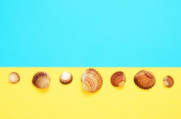 O mar descasca o teste padrão no fundo de papel de turquesa e de amarelo. conceito de verão.