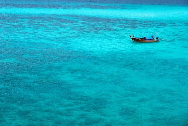 O mar parece azul esmeralda. há um barco flutuando silenciosamente nas ondas no mar de andaman. na praia do sol, koh lipe, satun, sul da tailândia