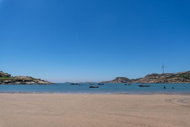 O mar sob o céu azul, praias limpas e água do mar, assim como ilhas e moinhos de vento