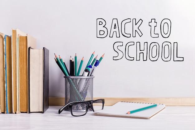 O marcador de inscrição em um quadro branco, back to school uma mesa com atributos de livros e óculos para escrever.
