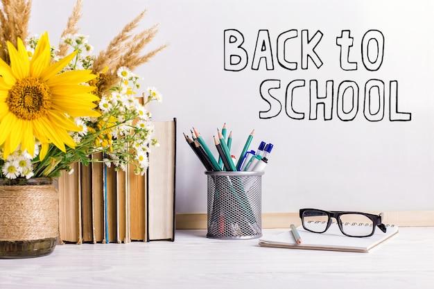 O marcador de inscrição em um quadro branco, back to school uma mesa com livros, um buquê de flores, óculos e atributos para a escrita.