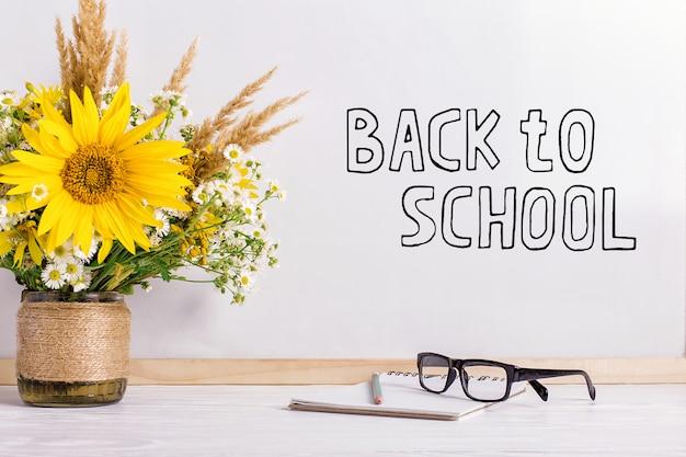 O marcador de inscrição em um quadro branco, de volta à escola uma mesa com um buquê de flores, copos e atributos para a escrita.
