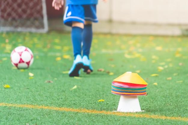 O marcador do cone e da cor no treinamento do futebol firled com o jogador de futebol no fundo para o conceito do treinamento do esporte.