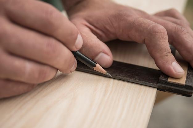 O marceneiro marca a peça de trabalho com um lápis. marcenaria