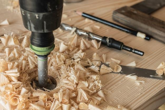 O marceneiro perfura uma peça de madeira com uma broca. uma broca, um lápis e um canto