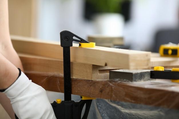 O marceneiro prende as peças de madeira na bancada. o vise está instalado no ambiente de trabalho. processamento cuidadoso e acabamento de produtos de madeira usando ferramentas especiais de carpintaria. redimensionando madeira de forma e aparência