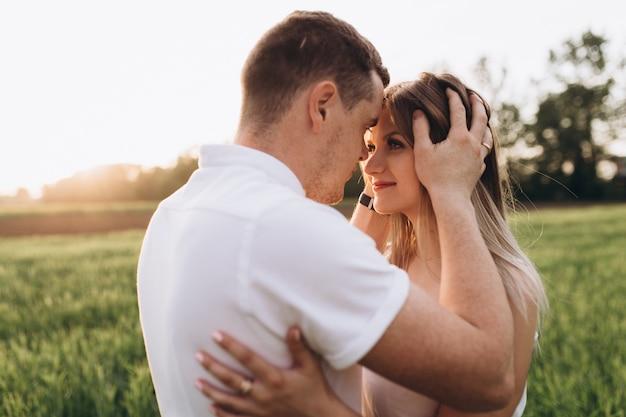O marido beijando sua esposa e de pé no campo