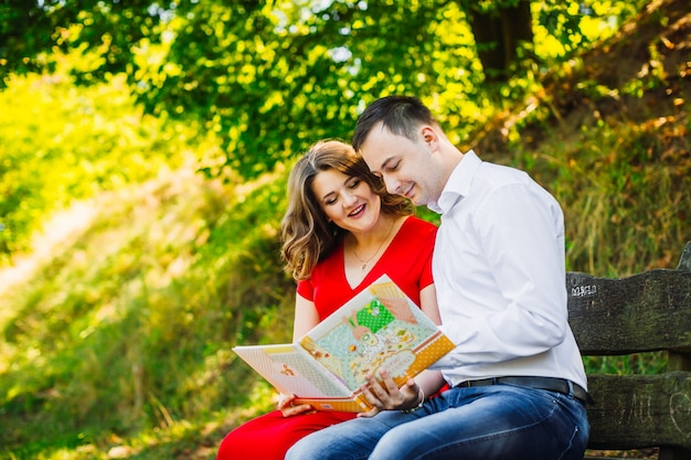 O marido com a esposa grávida sentada no banco