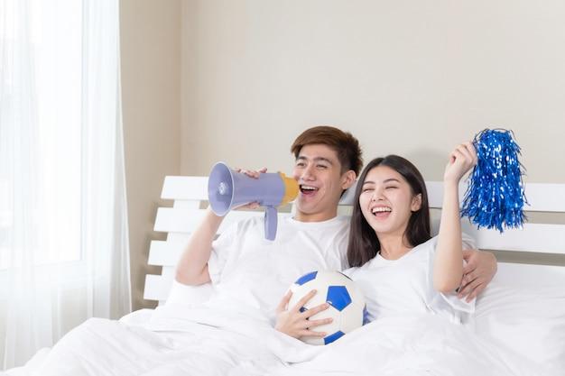 O marido considerável asiático novo e a esposa bonita sentem grande torcendo por sua equipe