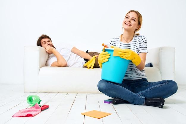 O marido deita no sofá enquanto sua esposa limpa a decoração