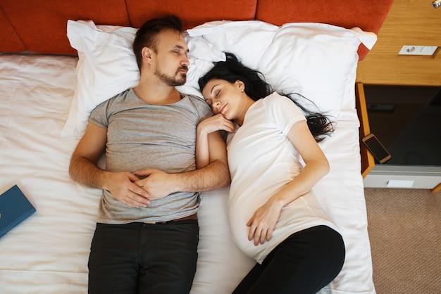 O marido e a esposa grávida com barriga estão dormindo na cama em casa. gravidez, período pré-natal. mamãe e papai expectantes estão descansando no sofá, assistência médica