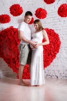 O marido e a esposa grávida no coração vermelho