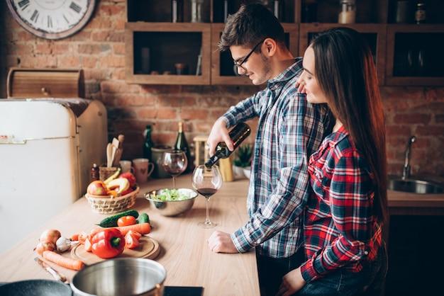 O marido serve vinho em uma taça e a família prepara um jantar romântico. casal prepara um jantar romântico juntos. salada de legumes cozinhando na cozinha. preparação de alimentos dietéticos frescos