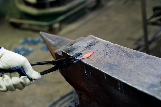 O martelo do ferreiro forja a flecha na bigorna