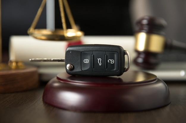 O martelo do leilão detalha a chave de um carro ao lado dele e um contrato