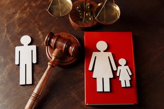 O martelo dos juízes divide as figuras familiares de madeira. livro de direito da família e divórcio