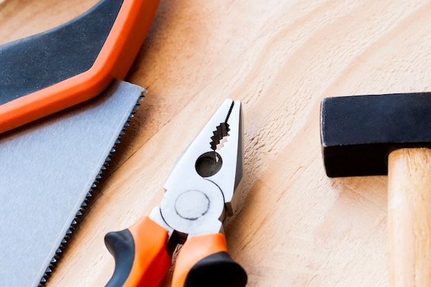 O martelo, os pregos e os alicates encontram-se em um fundo de madeira.