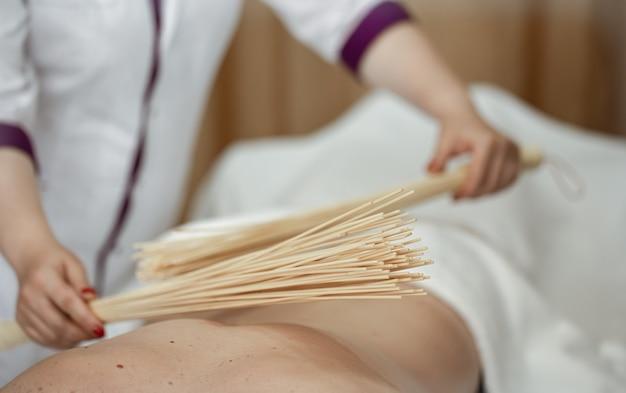 O massagista faz uma massagem japonesa em um homem com vassouras de bambu.