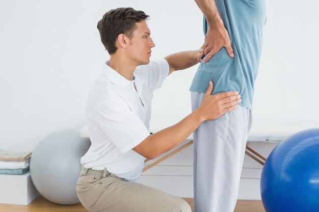 O massajador de terapeutas equipa a parte inferior das costas na academia hospitalar