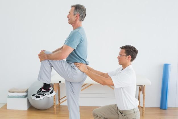 O massajador de terapeutas equipa a parte inferior das costas no ginásio hospital