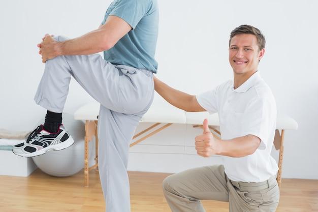 O massajador de terapeutas equipa as costas mais baixas enquanto gesticula polegares para cima