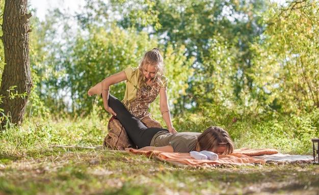 O massoterapeuta demonstra métodos de massagem refrescantes na natureza.