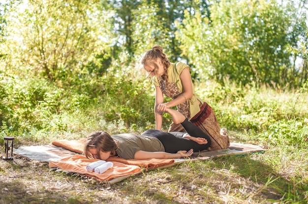 O massoterapeuta mestre oferece uma massagem completa na grama.