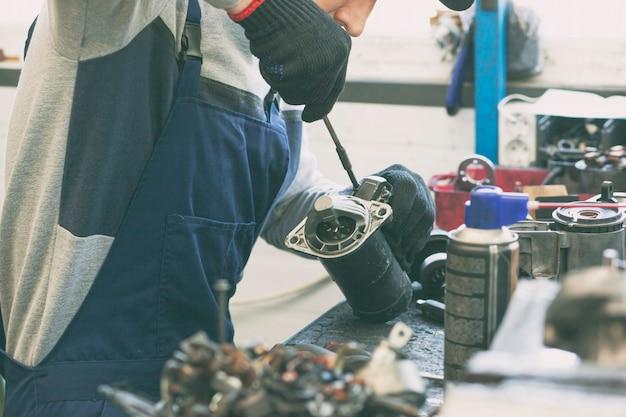 O mecânico consertando uma das peças do carro em funcionamento