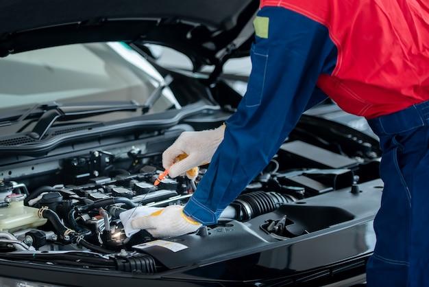 O mecânico de automóveis asiático em uma oficina de automóveis está verificando o motor. para os clientes que usam carros para serviços de reparo, o mecânico trabalha na garagem.