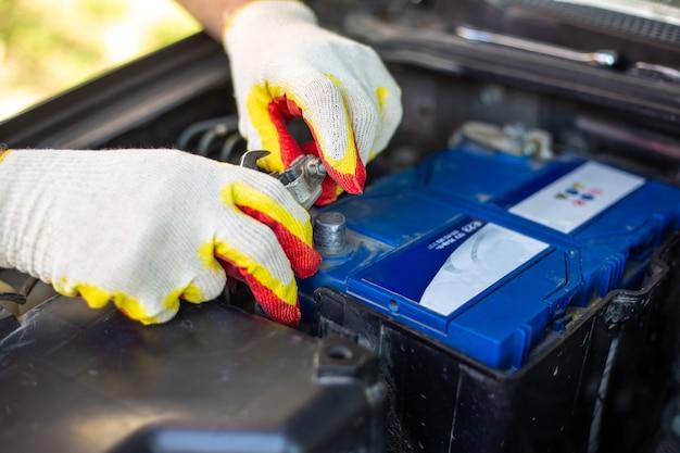 O mecânico de automóveis desatarraxa os parafusos da bateria do carro. instalação, substituição e reparação do acumulador.