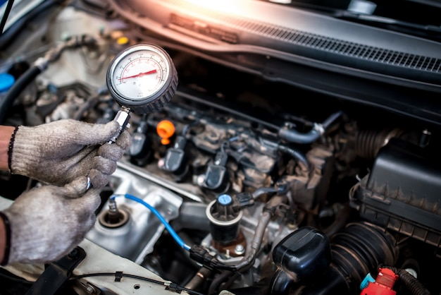 O mecânico de automóveis está prestes a medir a compressão no cilindro de um motor de carro usando um barômetro de diagnóstico e reparado na sala de máquinas de um veículo.