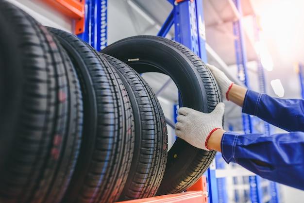 O mecânico de automóveis está trocando pneus novos em estoque para trocar para clientes na garagem - trocando rodas / pneus.