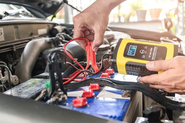 O mecânico de automóveis está usando um instrumento de medição de tensão e carregando a bateria