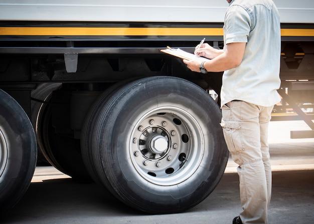 O mecânico de automóveis que segura a prancheta está verificando as rodas de um caminhão inspeção de pneus de caminhão de segurança