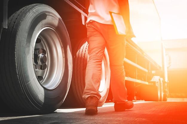 O mecânico de automóveis que segura a prancheta está verificando as rodas e os pneus de um caminhão. inspeção de segurança das rodas do caminhão