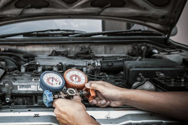 O mecânico de automóveis que usa a ferramenta de equipamento de medição para encher os condicionadores de ar do carro corrige a verificação.