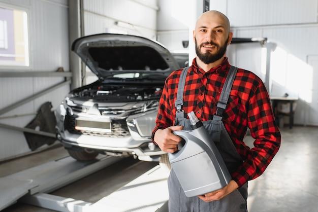O mecânico de automóveis substitui o óleo do carro