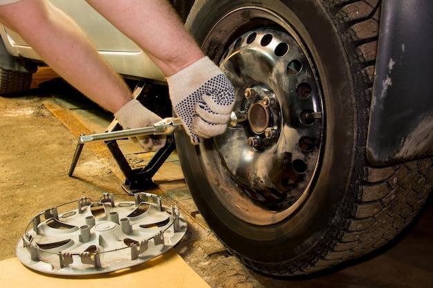 O mecânico desparafusa as porcas da roda. homem trocando o pneu. serviço de pneus. montagem de pneu.