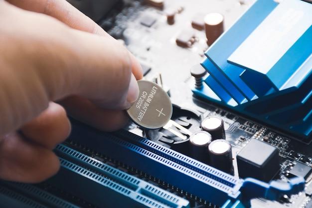 O mecânico do computador instala a bateria de lítio cr2025 no slot da bateria de backup cmos na placa-mãe do computador
