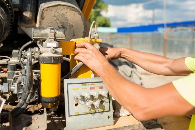 O mecânico do motorista troca o óleo em um compactador em um canteiro de obras, close-up