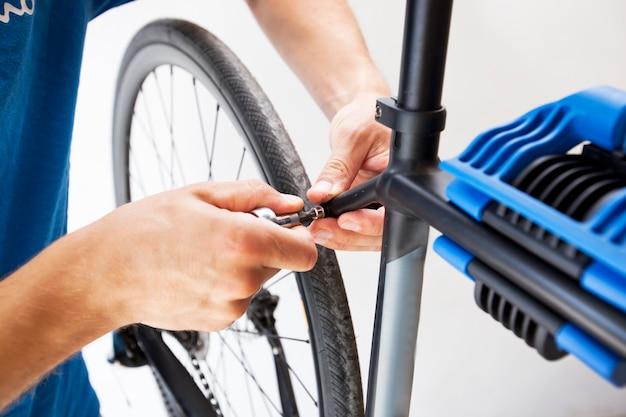 O mecânico está consertando a bicicleta de estrada em sua oficina