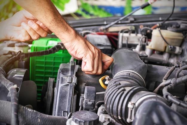 O mecânico está fechando a tampa do óleo do motor após adicionar o óleo ao motor até o nível