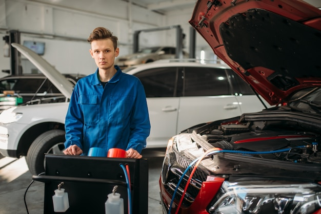O mecânico está no sistema de diagnóstico do ar condicionado. inspeção do condicionador no serviço do carro