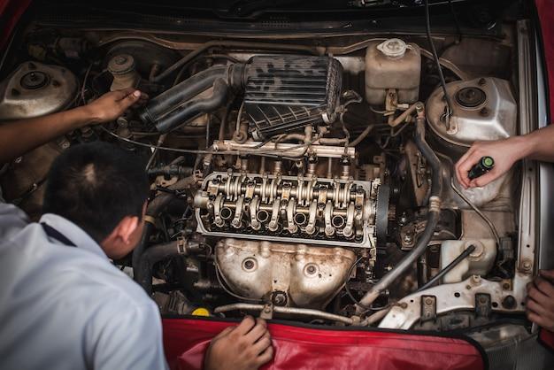 O mecânico está trabalhando para verificar os carros que trabalham no centro de serviço com uma empilhadeira. reparação e manutenção de automóveis