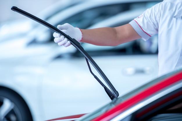 O mecânico está trocando os limpadores no estacionamento. troque os pneus do limpador para se preparar para a limpeza do pára-brisa enquanto chove durante a estação chuvosa.