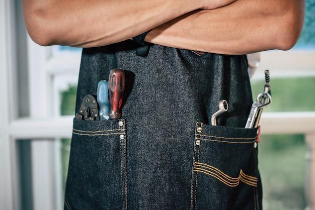 O mecânico está usando um avental preto e há ferramentas manuais na bolsa.