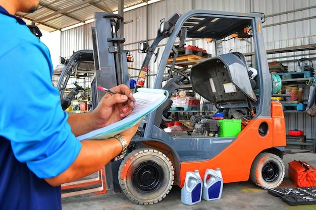 O mecânico está verificando a qualidade e o conceito de combustível para empilhadeira de manutenção.