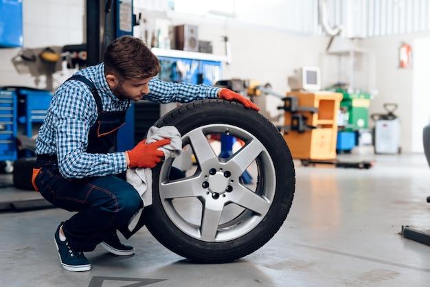 O mecânico novo limpa o pneu de carro na estação de serviço.