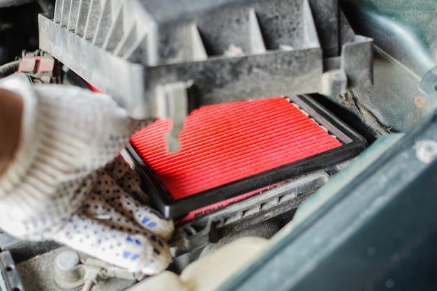 O mecânico substitui o filtro de ar no carro