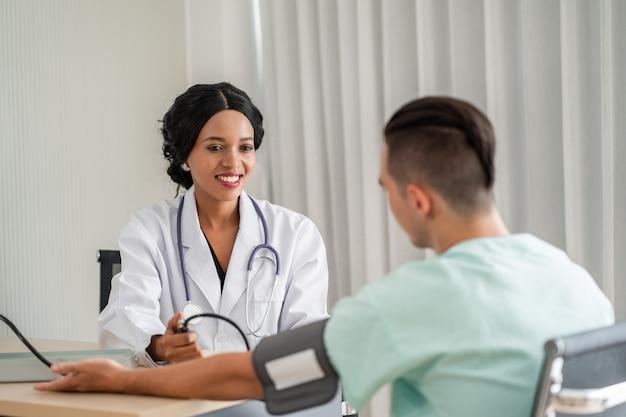 O médico afro-americano está medindo a pressão arterial do paciente. e fornecer consultas sobre tratamento aos pacientes